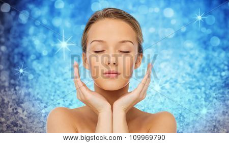 beauty, people, skincare and health concept - young woman face and hands over blue holidays lights or glitter background