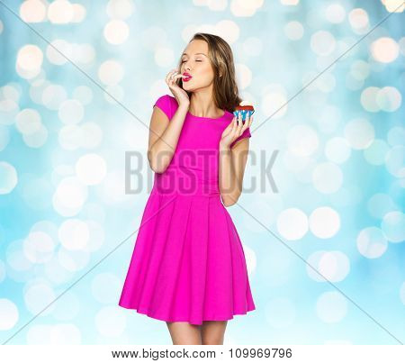 people, holidays, party, junk food and celebration concept - happy young woman in pink dress eating birthday cupcake over blue holidays lights background