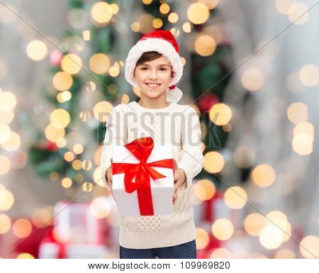 holidays, presents, christmas, childhood and people concept - smiling happy boy in santa hat with gift box over lights background