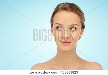 beauty, people and health concept - smiling young woman face and shoulders over blue background