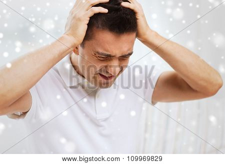 people, crisis, emotions and stress concept - unhappy man suffering from head ache at home over snow effect