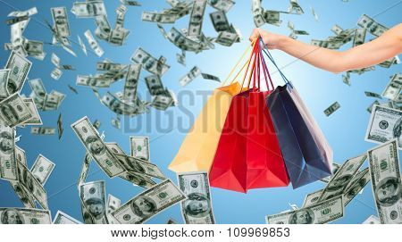 people, consumerism, finance and sale concept - close up of female hand holding shopping bags over blue background and money rain