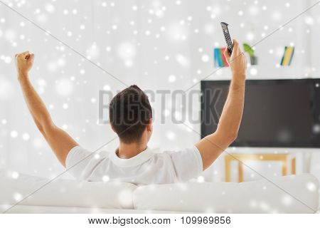 leisure, technology, mass media and people concept - man watching tv and supporting team at home from back over snow effect