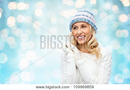 winter, fashion, christmas and people concept - smiling young woman in winter hat, sweater and gloves over blue holidays lights background