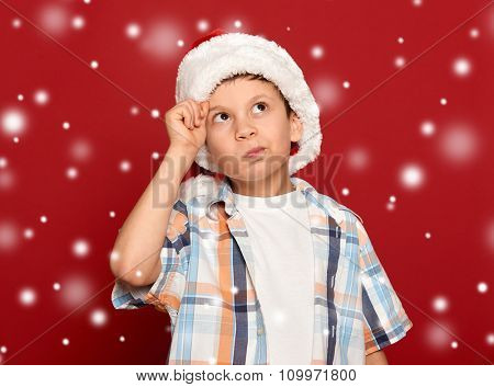 boy in santa hat have idea on red with snow