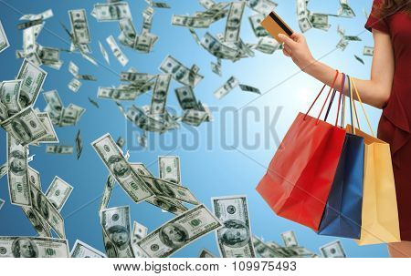 people, sale, finance and consumerism concept - close up of woman with shopping bags and bank or credit card over blue background and money rain