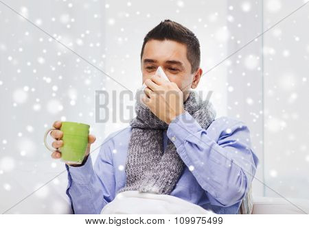 healthcare, flu, people, rhinitis and medicine concept - ill man blowing his nose with paper napkin and drinking tea at home over snow effect