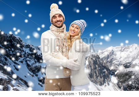 winter, fashion, couple, christmas and people concept - smiling man and woman in hats and scarf hugging over snowy mountains background