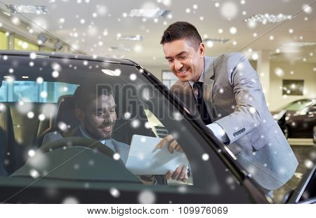 auto business, sale and people concept - happy man with dealer buying car in auto show or salon over snow effect