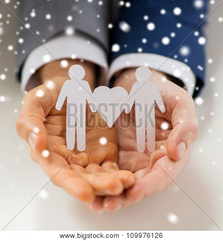 people, homosexuality, same-sex marriage and love concept - close up of happy male gay couple holding paper cutout love symbol over snow effect