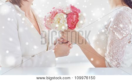 people, homosexuality, same-sex marriage and love concept - close up of happy married lesbian couple with flower bunch over snow effect