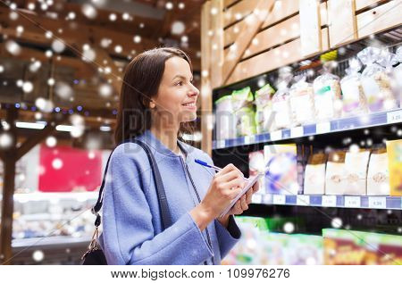 sale, shopping, consumerism and people concept - happy young woman taking notes to notebook in market over snow effect