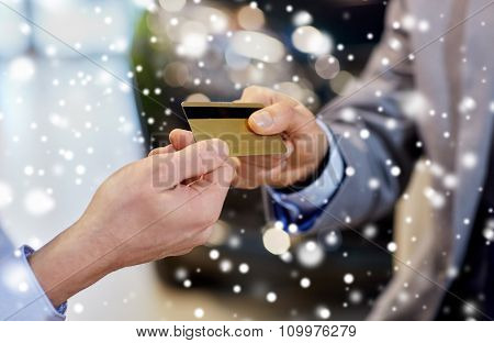 auto business, sale and people concept - close up of customer hand giving credit card to car dealer in auto show or salon over snow effect