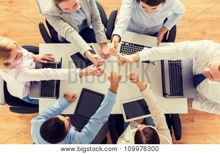business, people, technology and team work concept - close up of creative team with laptop and tablet pc computers showing thumbs up gesture and sitting at table in office