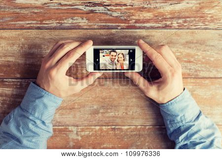 people, memory, relations and technology concept - close up of male hands holding smartphone with photo of happy couple on screen at table