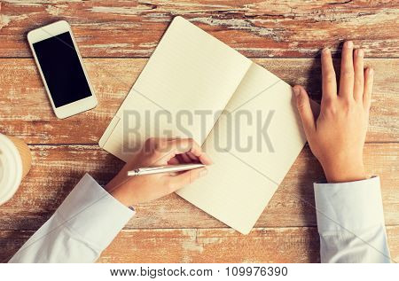 business, education, people and technology concept - close up of female hands with notebook and smartphone on table