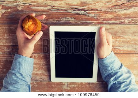 business, education, people and technology concept - close up of male hands with tablet pc computer and muffin on table