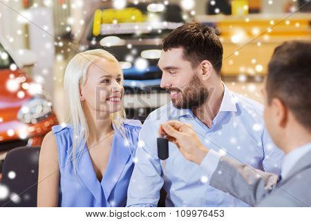 auto business, sale and people concept - happy couple with dealer giving car key in auto show or salon over snow effect