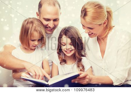 family, leisure, education and people - smiling mother, father and little girls reading book over snowflakes background