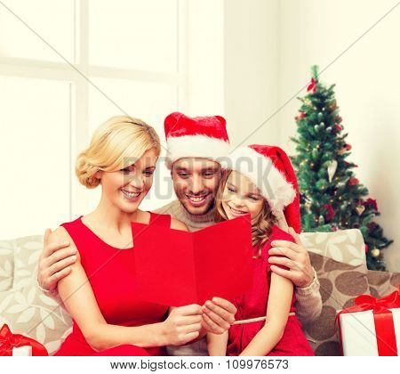 holidays, family and people concept - happy mother, father and little girl in santa helper hats with gift boxes reading geeting card over living room and christmas tree background