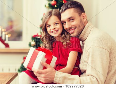 family, christmas, x-mas, happiness and people concept - smiling father and daughter holding gift box