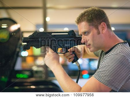 Man playing video shooting game at amusement park.