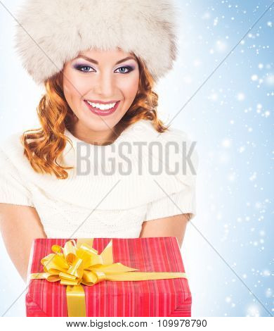 Attractive girl with a Christmas gift over winter background with snow.