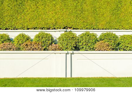 White stone fence with trimmed bush and green lawn.
