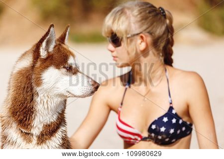 Young Girl Sits On The Beach With Dog