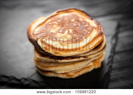 High pile of delicious pancakes on dark background