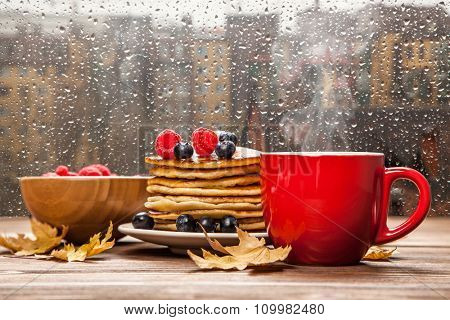Cup of coffee and pancakes with berries