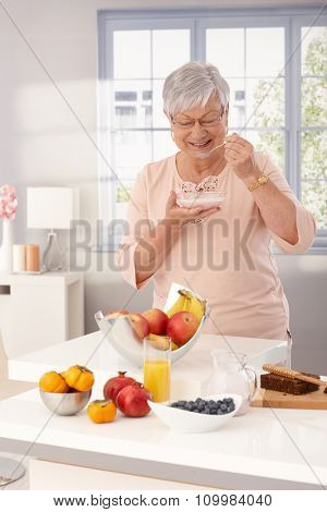 Mature woman standing by kitchen counter, eating breakfast cereal.