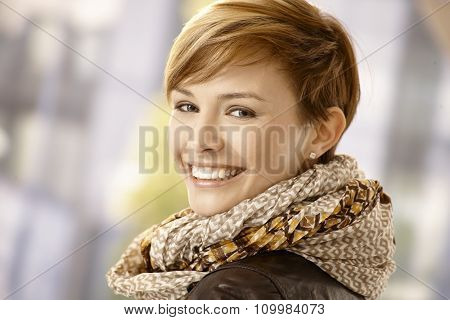 Happy young woman looking back and smiling