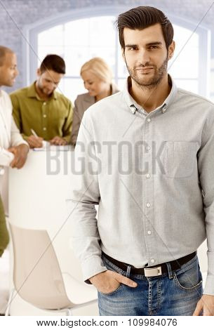 Portrait of confident young businessman standing hand in pocket.