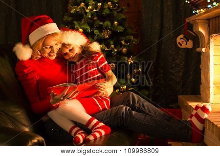 Middle-aged mother and her little daughter reading a book by a Christmas tree in cozy living room in