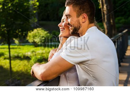 Guy and a girl hugging on a bridge in the beautiful park.