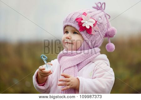 A Cute Little Girl Blows Bubbles In Autumn