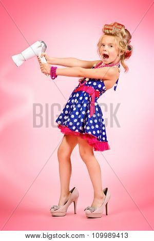 Full length portrait of a cute funny little pin-up girl in hair curlers with a hairdryer in the hand. Pink background.