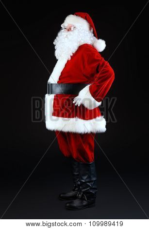 Full length portrait of Santa Claus standing sideways over black background. Christmas time.