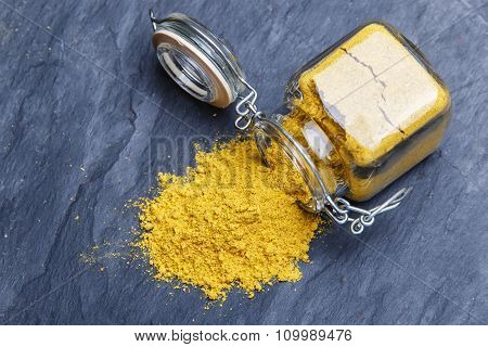 powder seasoning spice turmeric on a black stone