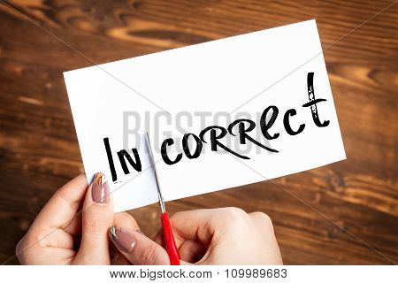 Woman hands cutting card with the word incorrect