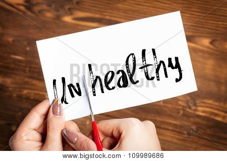 Woman hands cutting card with the word unhealthy