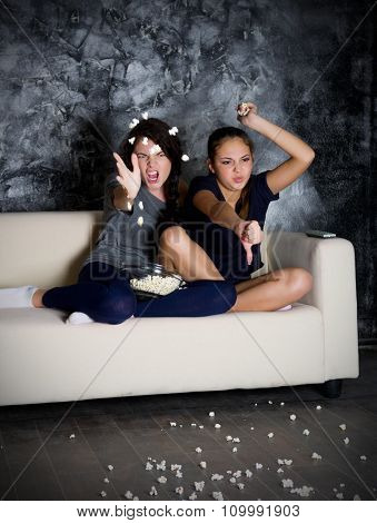 Two angry girls looks TV in dark room