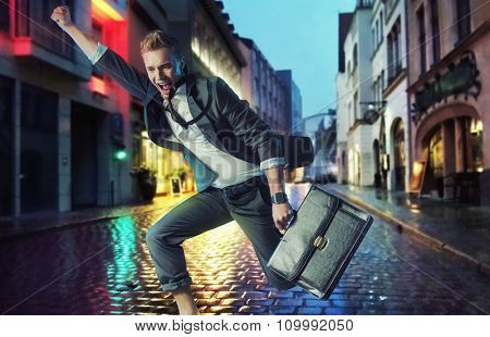 Happy businessman running on a rainy street