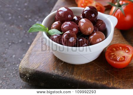 Italian food still life - olives, tomatoes, basil, prosciutto ham