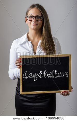 Capitalism - Young Businesswoman Holding Chalkboard With Text
