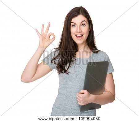 Young woman hold with notebook computer and showing with ok sign gesture