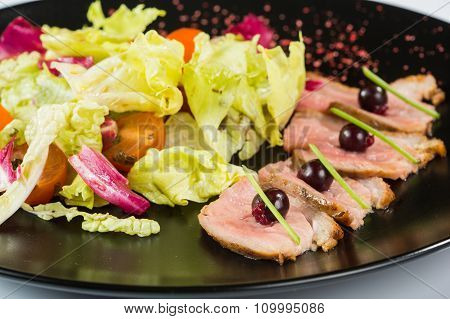 grilled meat with lettuce. on black plate