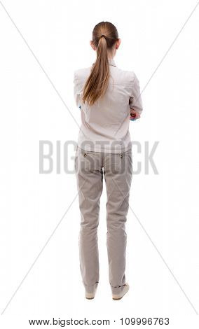 back view of standing young beautiful  woman. girl watching. Rear view people collection.  backside view of person. Girl with long hair in a white jacket standing with her hands folded on his stomach