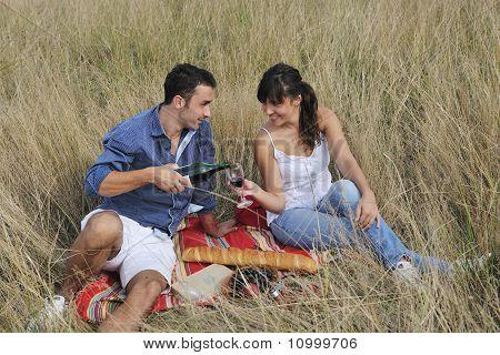 Glückliches Paar genießen Landschaft Picknick im hohen Gras